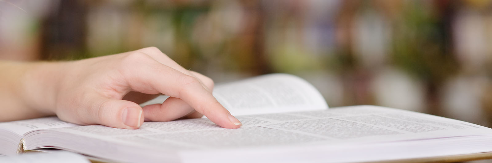 hand pointing to page in a book