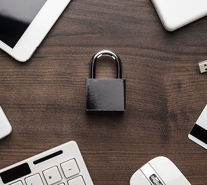 padlock on a table with electronic devices surrounding it